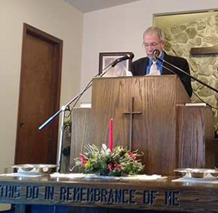 "Pastor Jack Emmite leads worship in Antioch Baptist's temporary meeting place stating, ""We're taking one step at a time and will wait on the Lord."""
