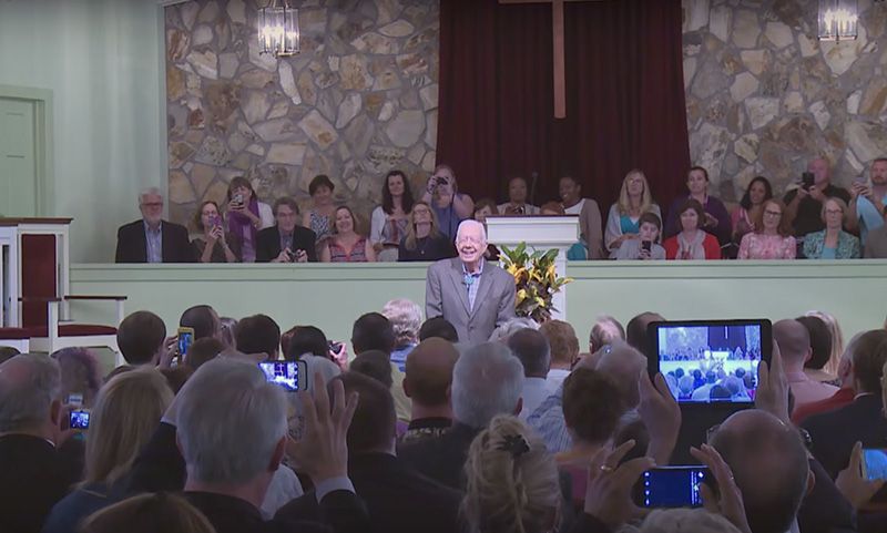 Guests take photos of former President Jimmy Carter at the beginning of a Sunday school class at Maranatha Baptist Church in Plains, Ga. Screenshot from YouTube