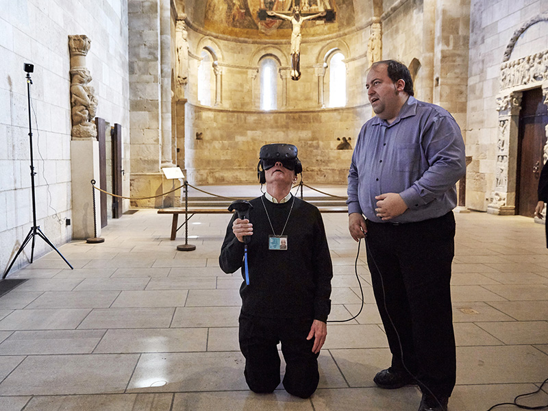 "The Rev. Xavier Seubert, left, of the Friary of St. Francis of Assisi in Manhattan explores the interior of an intricately carved prayer bead using a VR headset, guided by Joseph Ellsworth of the Canadian Film Center, on April 3, 2017. The exhibit ""Small Wonders: The VR Experience"" at The Met Cloisters Museum in New York City is an immersive experience that takes museum patrons inside a miniature, wooden prayer bead using micro-CT imaging technology and a VR headset. RNS photo by Steve Remich"