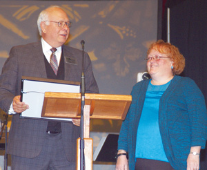 Missouri Baptist Convention Executive Director John Yeats (left) presents Tanya McMillan, administrative assistant for the Church Strengthening Team, with a plaque recognizing her 25 years as a convention employee. The convention also presented her with flowers. She has served in various roles since joining the convention staff Jan. 1, 1990.