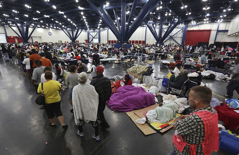 People line up for food as others rest at the George R. Brown Convention Center that has been set up as a shelter for evacuees escaping the floodwaters from Tropical Storm Harvey in Houston on Aug. 29, 2017. (AP Photo/LM Otero)