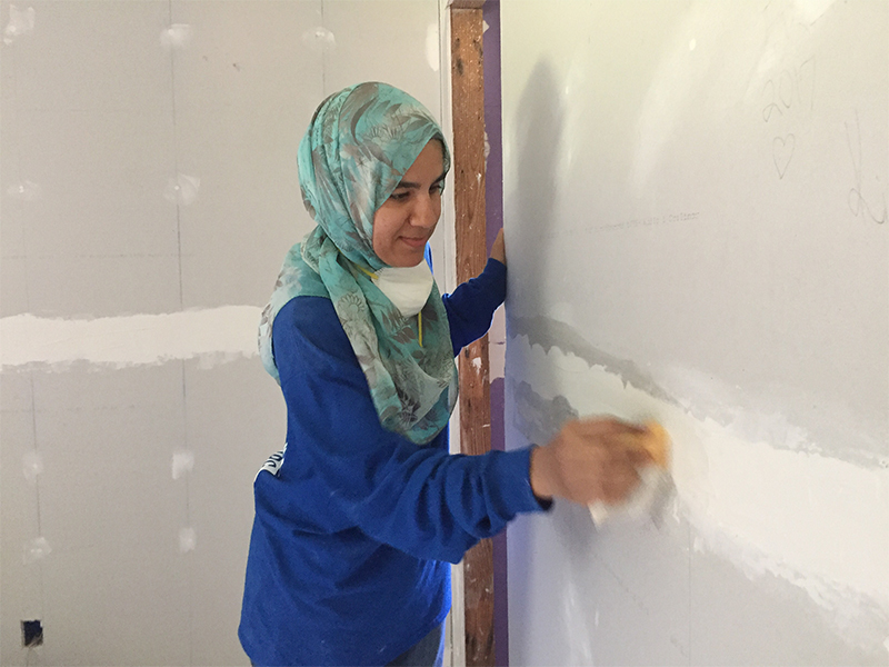 Amaney Kazlak of Jersey City, N.J.,, an Islamic Relief USA volunteer, uses a sanding sponge to smooth out the newly installed drywall in a home in Princeville, N.C. RNS photo by Yonat Shimron