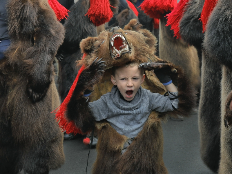 A child wearing a bear fur costume yawns during a parade of new year's rituals in Comanesti, northern Romania, Saturday, Dec. 30, 2017. The tradition, originated in pre-Christian times, when dancers in costumes or animal furs, went from house to house in villages singing and dancing to ward off evil.(AP Photo/Vadim Ghirda)