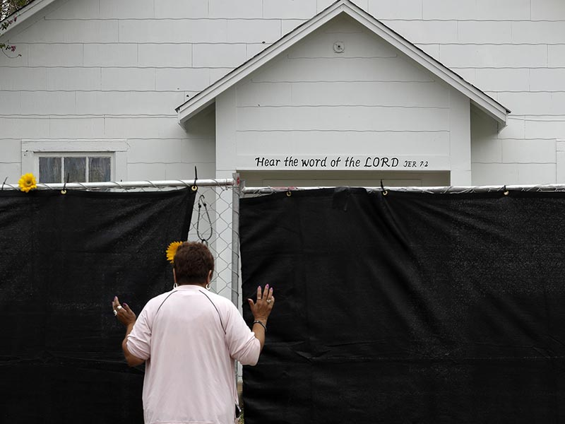 A woman prays outside of the Sutherland Springs First Baptist Church, Sunday, Nov. 12, 2017, in Sutherland Springs, Texas, a week after a man opened fire inside the church. Hundreds of people gathered in the tiny town for a Sunday service at a tent erected in a baseball field. (AP Photo/Eric Gay)