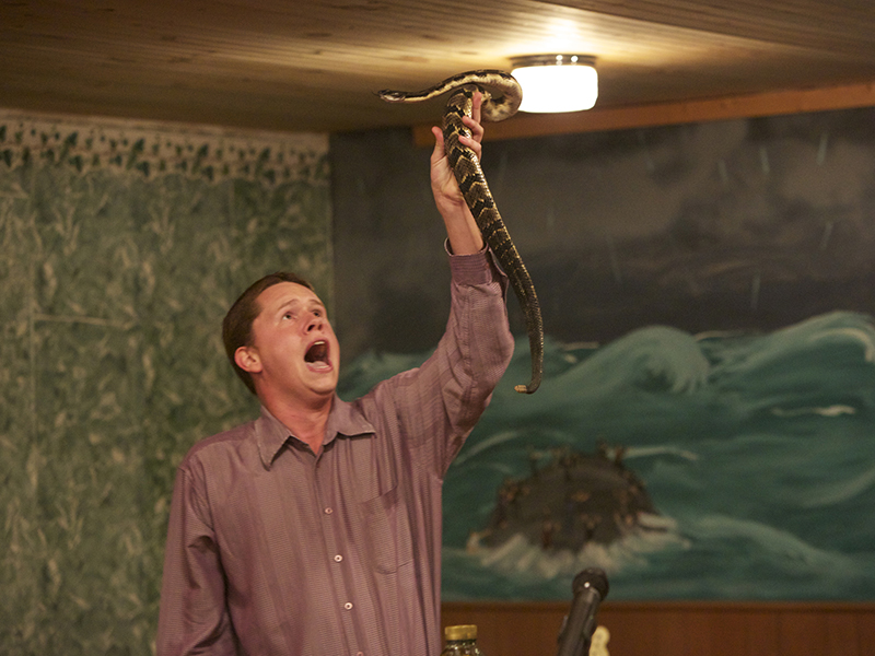 Andrew Hamblin preaches while holding a snake above his head in LaFollette, Tenn. Photo courtesy of National Geographic Channels