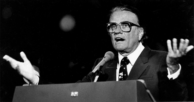 """Billy Graham preaches before a crowd of 40,000 at the Southern Baptist Convention in the Louisiana Superdome, June 14, 1982. Speaking at a public evangelistic rally sponsored by the Southern Baptist Pastors Conference as a preliminary to the Southern Baptist Convention meeting here, the world famous evangelist said, """"the chances of any of us ever seeing the year 2000 are very remote without God's intercession."""" Photo by Chuck Cook/New Orleans Times Picayune"""