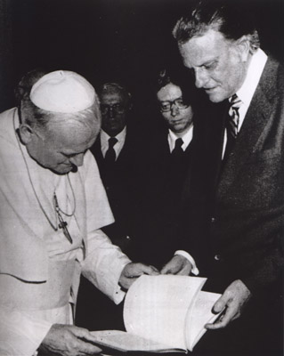 Billy Graham presents a book to Pope John Paul II during an audience on Jan 12., 1981, at the Vatican. Graham gave the pontiff photo albums of the Philippines and Japan — countries that the pope visited shortly after that. Religion News Service file photo