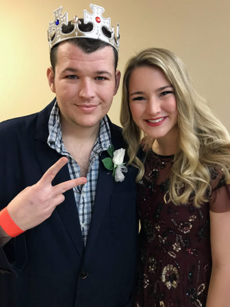 """""""King"""" Arthur Jennings, 27, left, with his volunteer buddy Addison Paxton, a University of Oklahoma student, is a big fan of Tim Tebow, even though he cheers for the OU Sooners. Jennings was looking forward to dancing at the """"Night to Shine"""" event hosted by the Putnam City Baptist Church in Oklahoma City on Feb. 9, 2018. RNS photo by Bobby Ross Jr."""