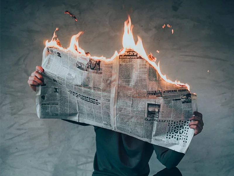 A photo illustration of a newspaper in flames. Photo by Elijah O'Donell via Unsplash/Creative Commons