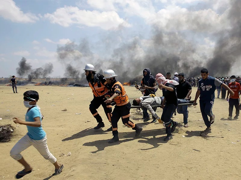 Palestinian medics and protesters evacuate a wounded youth during a protest at the Gaza Strip's border with Israel, east of Khan Younis, Gaza Strip, on May 14, 2018. Thousands of Palestinians are protesting near Gaza's border with Israel, as Israel prepared for the festive inauguration of a new U.S. Embassy in contested Jerusalem. (AP Photo/Adel Hana)