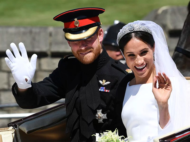 Britain's Prince Harry, Duke of Sussex, and his wife, Meghan Markle, Duchess of Sussex, wave from the Ascot Landau Carriage during their carriage procession on Castle Hill outside Windsor Castle in Windsor, England, after their wedding ceremony on May 19, 2018. (Paul Ellis/pool photo via AP)