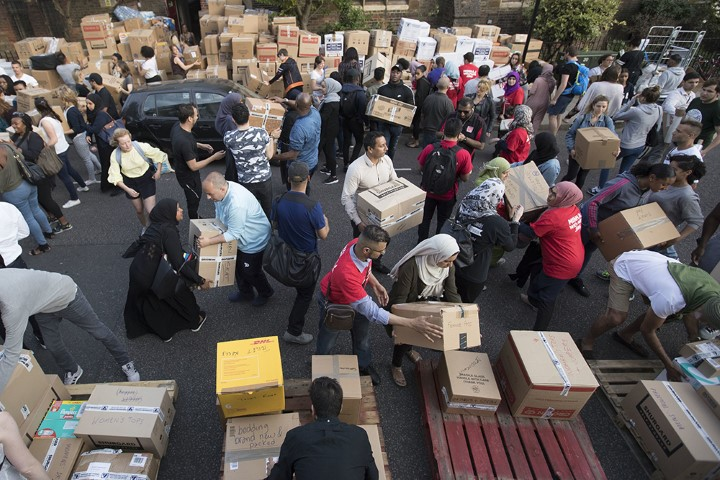 Volunteers organise donations near Grenfell Tower in west London, on June 15, 2017. A massive fire raced through the 24-storey high-rise apartment building in west London the day before. (AP Photo/Tim Ireland)
