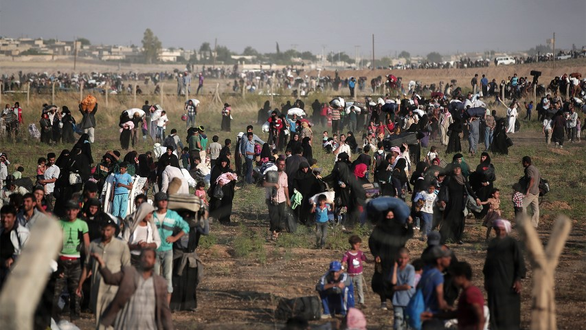 In this June 14, 2015 file photo taken from the Turkish side of the border between Turkey and Syria, in Akcakale, Sanliurfa province, southeastern Turkey, thousands of Syrian refugees walk in order to cross into Turkey. (AP Photo/Lefteris Pitarakis)