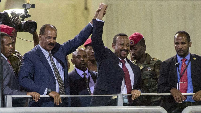 Eritrean President Isaias Afwerki, left, and Ethiopia's Prime Minister Abiy Ahmed, center, hold hands as they wave at the crowds in Addis Ababa, Ethiopia, on July 15, 2018. Official rivals just weeks ago, the leaders of Ethiopia and Eritrea have embraced warmly to the roar of a crowd of thousands at a concert celebrating the end of a long state of war. (AP Photo/Mulugeta Ayene)