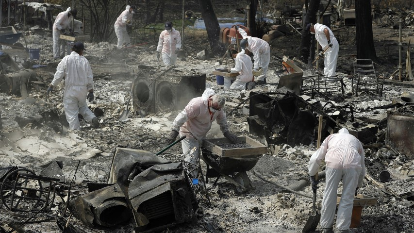 Volunteers with Samaritan's Purse sift through the charred remains of a home burned in the Carr Fire on Aug. 10, 2018, in Redding, Calif. (AP Photo/John Locher)