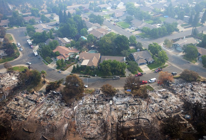 Homes destroyed by a wildfire are seen from an aerial view in the Keswick neighborhood of Redding, Calif., on Aug. 10, 2018. Fire crews have made progress against the biggest blaze in California history but officials say the fire won't be fully contained until September. (AP Photo/Michael Burke)