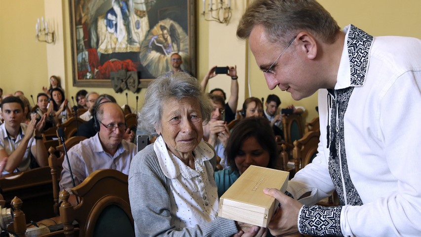 Andriy Sadoviy, right, the mayor of Lviv, Ukraine, presents a glass copy of an old metal synagogue key to Yanina Hescheles, Polish writer and a Nazi concentration camp survivor, at a ceremony Sept. 2, 2018, marking the 75th anniversary of the annihilation of the city's Jewish population by Nazi Germany. Lviv, once a major center of Jewish life in Eastern Europe, is commemorating the anniversary and honoring those working today to preserve that vanished world. The commemoration comes amid a larger attempt in Ukraine to preserve the memories of the prewar Jewish community. (AP Photo/Yevheniy Kravs)
