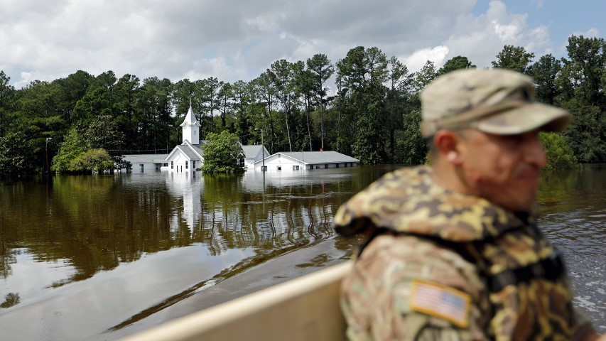 A church sits flooded as U.S. Army Spc. Daniel Ochoa rides in the back of a high-water vehicle while searching for residents to evacuate in the aftermath of Hurricane Florence in Spring Lake, N.C., on Sept. 17, 2018. (AP Photo/David Goldman)