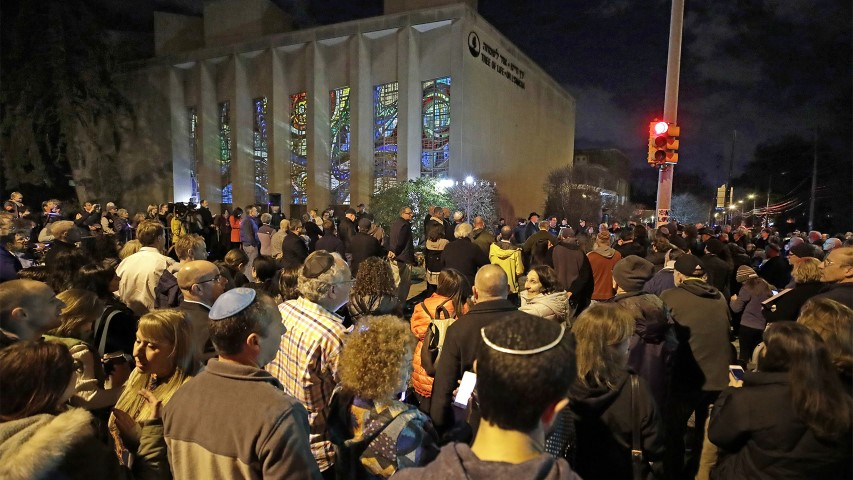 Rabbi Jeffrey Myers leads a gathering in Hanukkah songs after lighting a menorah outside the Tree of Life synagogue on the first night of Hanukkah, Dec. 2, 2018, in the Squirrel Hill neighborhood of Pittsburgh. A gunman shot and killed 11 people while they worshipped on Oct. 27, 2018, at the temple. (AP Photo/Gene J. Puskar)