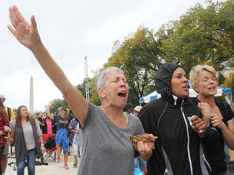 "Women prayed for racial reconciliation at the ""Rise Up"" prayer rally on Oct. 9, 2017, in Washington, D.C. Left to right are Beth Defrance of Colorado Springs, Colo., Akiliah Manuel Mills of Riverside, Calif., and Valerie Jungck of Colorado Springs, Colo. RNS photo by Adelle M. Banks"