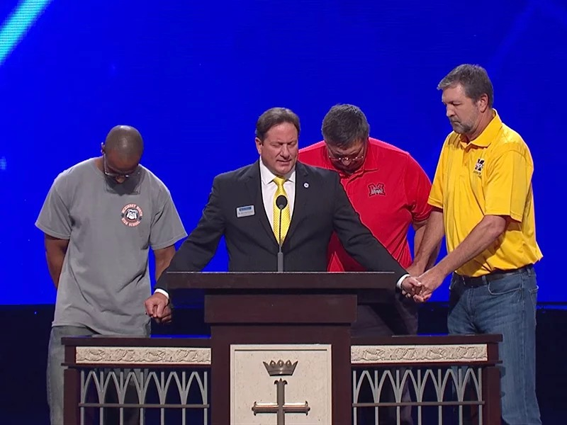 Rick McDaniel, center, superintendent of McKinney, Texas, public schools, prays at a mandatory employee meeting at Prestonwood Baptist Church in nearby Plano, Texas, in August 2017. Screenshot via McKinney schools video