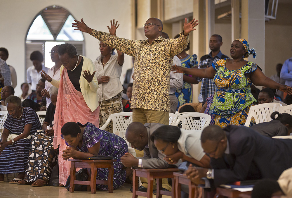 Rwandans sing and pray at the Evangelical Restoration Church in the Kimisagara neighborhood of the capital, Kigali, Rwanda, on April 6, 2014. Rwanda's government has closed numerous churches and mosques in 2018 as it seeks to assert more control over a vibrant religious community whose sometimes makeshift operations, authorities say, have threatened the lives of followers. (AP Photo/Ben Curtis)