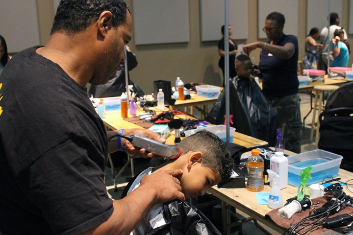 Stylist Tony Coursey cuts the hair of 4-year-old Trend Cooper, grandson of Pamela Jennings, at People's Church in Oklahoma City on July 28, 2018. RNS photo by Bobby Ross Jr.