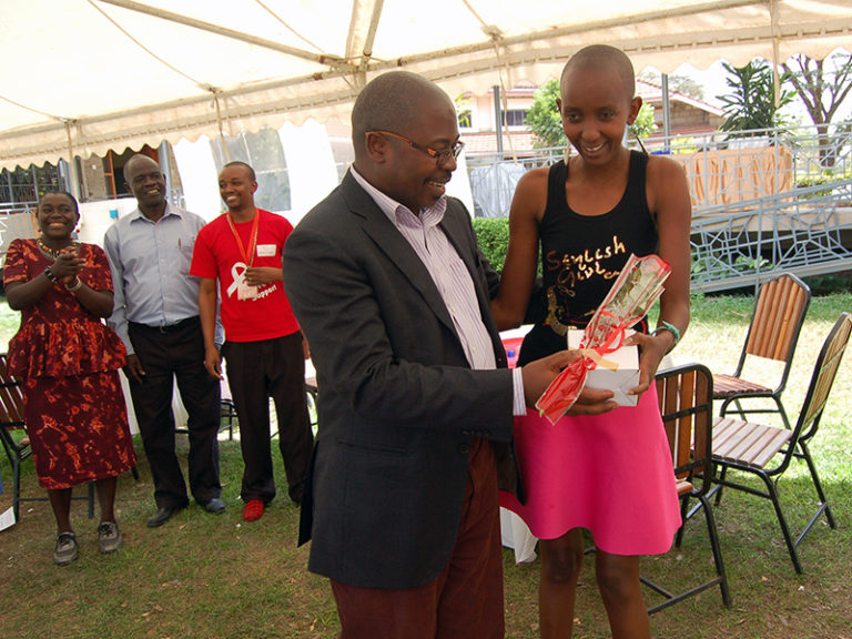 he Rev. Geoffrey Wanjala Munialo hands a rose and gift to Mary Mutua, a youth living with HIV, on Valentine's Day in Nairobi, Kenya, on Feb. 14, 2017. RNS photo by Fredrick Nzwili