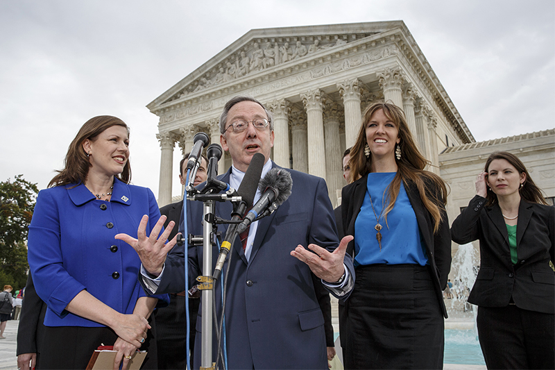 Attorney Douglas Laycock, center, characterizes his argument before the Supreme Court on behalf of an Arkansas prison inmate who says his Muslim beliefs that require him to grow a beard are being violated by prison rules that prevent beards on Oct. 7, 2014, in front of the court in Washington. Laycock, a professor at the University of Virginia School of Law, is working with the Beckett Fund for Religious Liberty which prevailed in the Hobby Lobby case last June. At left is Hannah Smith, a senior counsel with the Becket Fund. At right is Emily Hardman and Diana Verm, far right, both of the Beckett Fund. (AP Photo/J. Scott Applewhite)