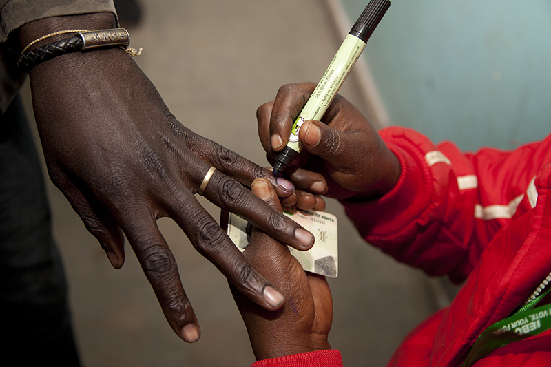 A polling official marks a voter's finger after he cast his vote at a polling station in Nairobi, Kenya, on Aug. 8, 2017. (AP Photo/ Sayyid Abdul Azim)