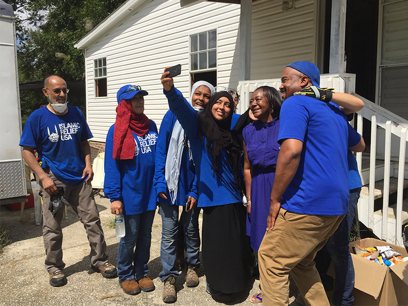 A group of volunteers with Islamic Relief USA take a selfie with Delores J. Porter,whose house was submerged in water after Hurricane Matthew flooded the town of Princeville. RNS photo by Yonat Shimron
