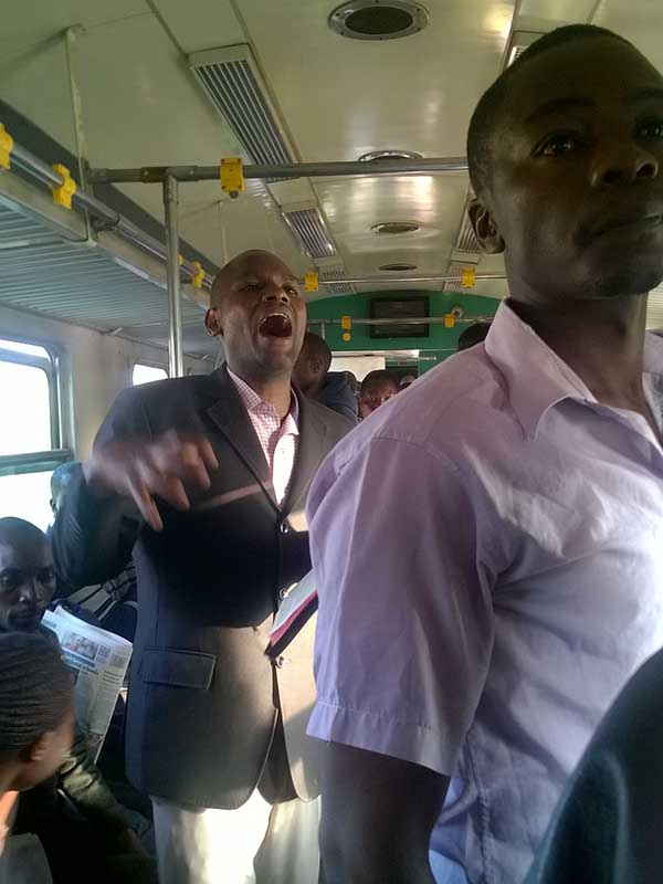 A preacher delivering the sermon on one of the coaches to Nairobi, Kenya, on Sept. 27, 2017. Several preachers lead worship on the train. Photo by Fredrick Nzwili