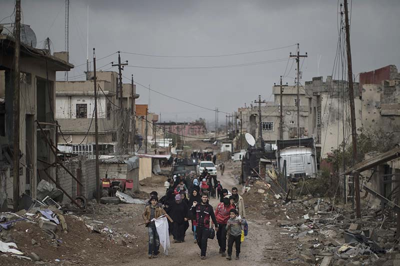 In this March 13, 2017 file photo, Iraqi civilians flee their homes during fighting between Iraqi security forces and militants of the Islamic State group, on the western side of Mosul, Iraq. AP Photo/Felipe Dana