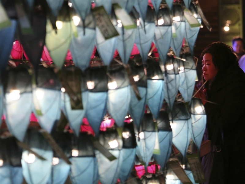 A woman prays in front of lanterns to celebrate the New Year at Jogyesa Buddhist temple in Seoul, South Korea, Sunday, Dec. 31, 2017. (AP Photo/Ahn Young-joon).