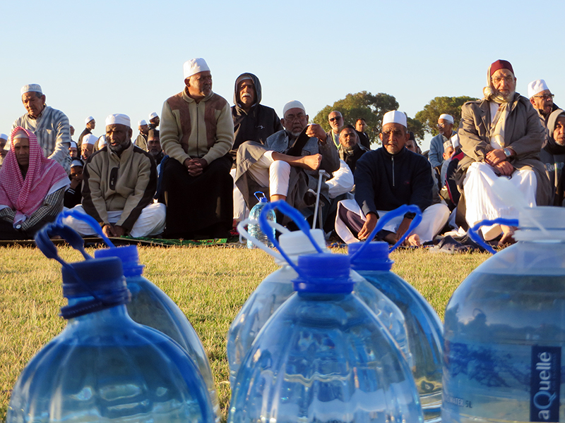 The Muslim Judicial Council South Africa joined Habibia Soofie Masjid and Masjidul-Quds to lead more than 1,000 Muslims in an early morning prayer for rain at the Rylands sports complex in Athlone, Cape Town, on Feb. 4, 2018. Worshippers donated bottled water, foreground, and many mosques throughout Cape Town have installed aerators on taps or are providing worshippers with spray bottles or single cups of water to perform ablutions. RNS photo by Brian Pellot