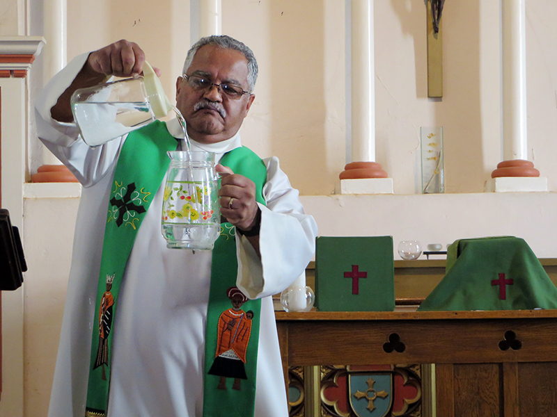 The Anglican bishop of Table Bay, the Rt. Rev. Garth Q. Counsell, slowly pours one pitcher of water into another before beginning his sermon at Zonnebloem Estate's chapel during the Anglican Diocese of Cape Town's Water (In)Justice Conference on Feb. 3, 2018. RNS photo by Brian Pellot