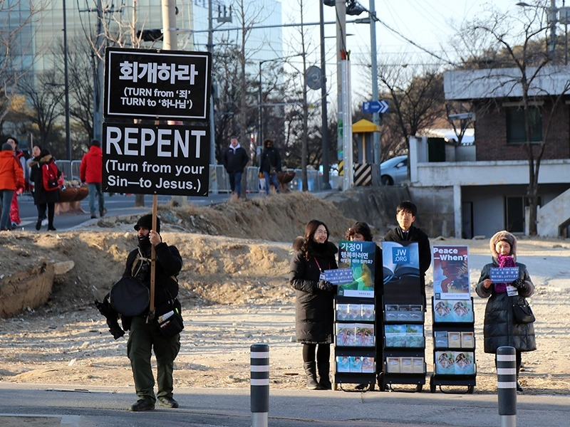 Jehovah's Witness volunteers, right, distribute materials as an independent street preacher passes by, left, on Feb. 10, 2018, near Olympic venues in Gangneung, South Korea. (RNS photo: Madeline C. Mulkey)