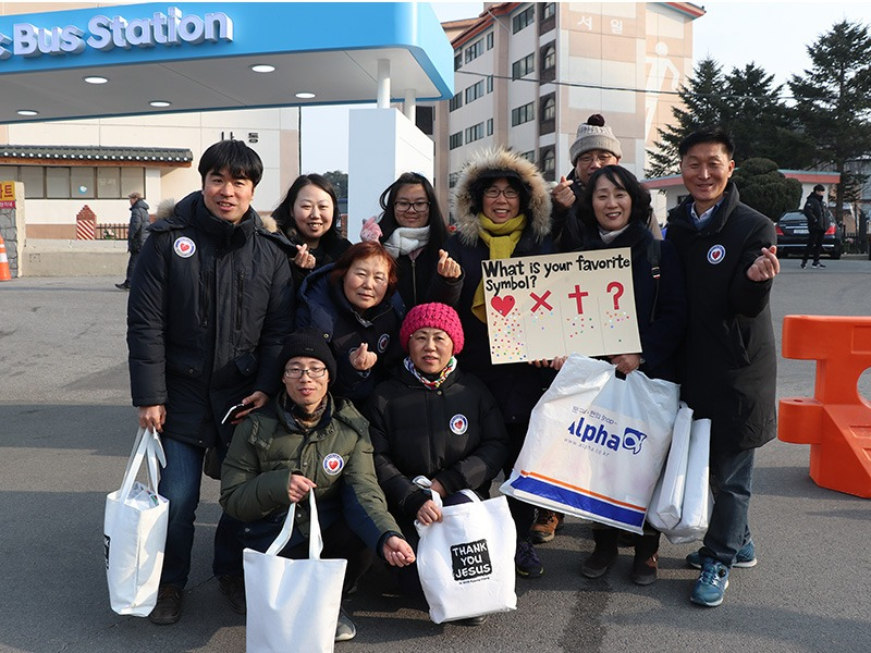 Volunteers with Cru (Campus Crusade for Christ) stand at the bus station by Olympic Park,  asking spectators their favorite symbol, and using it as a connection to start a conversation on religion, on Feb. 8, 2018, in South Korea. (RNS photo: Madeline C. Mulkey)