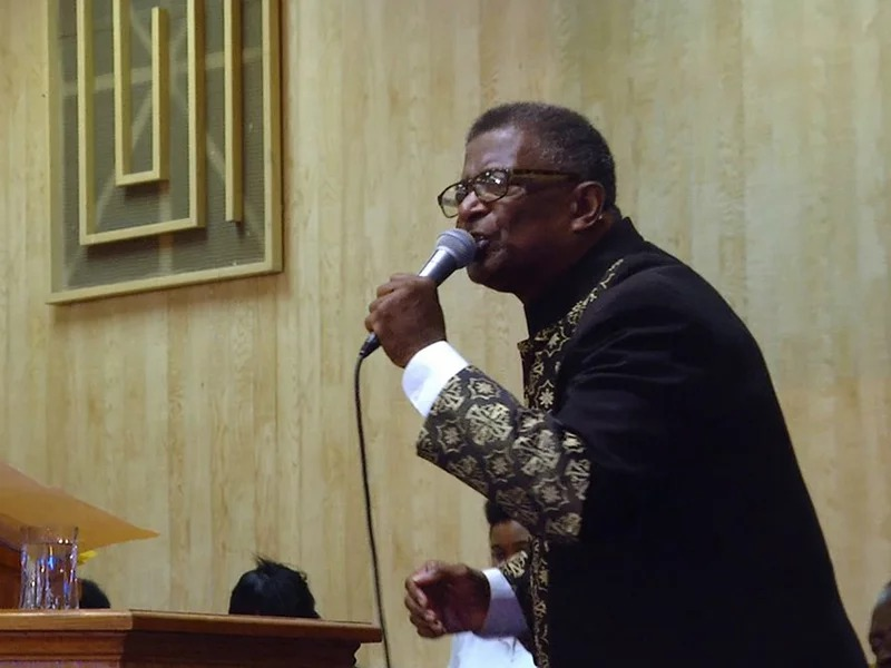 """Pastor Vernal Harris preaches to his congregation in upstate New York. Along with wife, Narseary, he struggles with his faith following the loss of their two sons. Photo by Paul Sanderson/""""Into the Night: Portraits of Life and Death"""""""