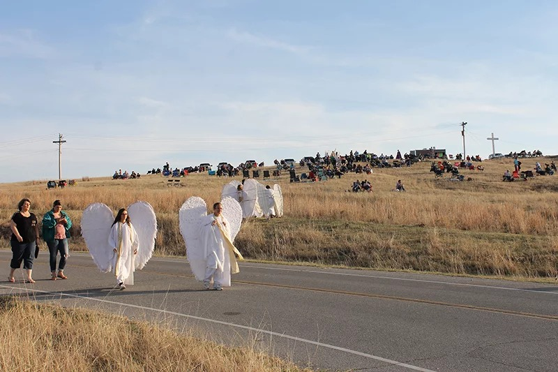 "Angels McKinsey Green, 17, left, and her mother, Lisa Green, walk up the street as the crowd gathers on the hillside for the ""Prince of Peace"" Easter pageant at Holy City of the Wichitas in southwestern Oklahoma on March 24, 2018. RNS photo by Bobby Ross Jr."