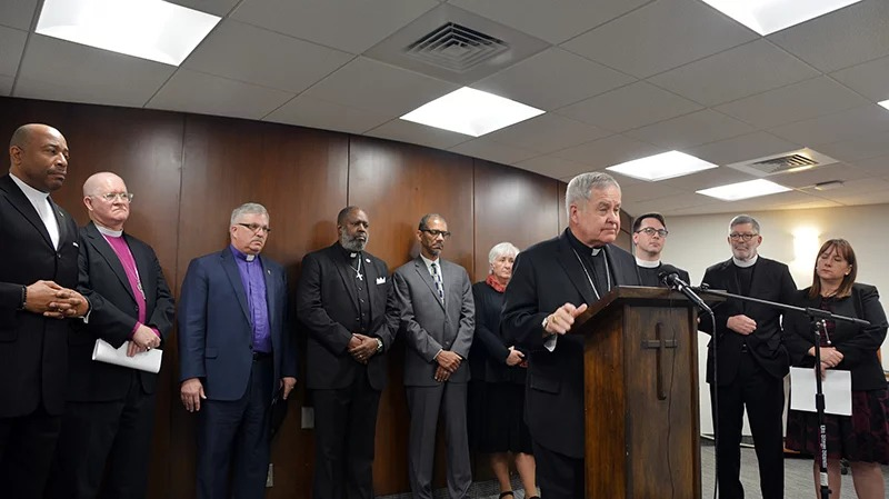 Religious leaders from a variety of faiths join Archbishop Robert J. Carlson, at podium, to express opposition to a Missouri bill that would permit people to carry concealed firearms in church, during a news conference in St. Louis, on April 11, 2018. Photo courtesy of Fred Koenig
