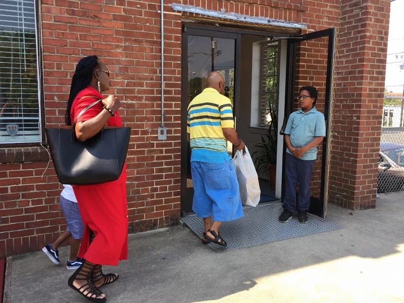 Kwame Cannon Jr., 11, right, greets worshippers at Faith Community Church in Greensboro, N.C., on May 13, 2018. The church shares space with several nonprofits in an old community center building. Three years ago solar panels were installed on the roof of the building. RNS photo by Yonat Shimron