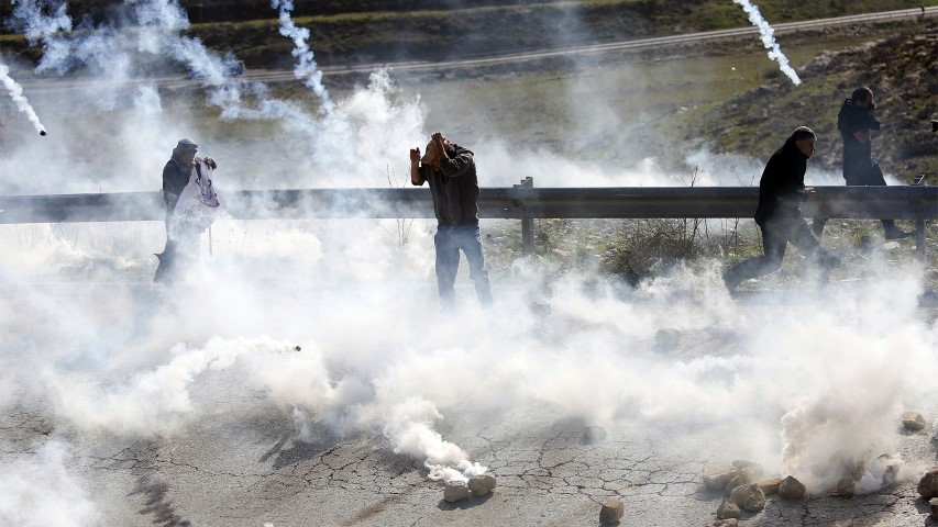 Palestinian demonstrators run from tear gas fired by Israeli troops during clashes following a demonstration in support of Palestinian prisoners in Nabi Saleh near the West Bank city of Ramallah, on Jan. 13, 2018. (AP Photo/Majdi Mohammed)