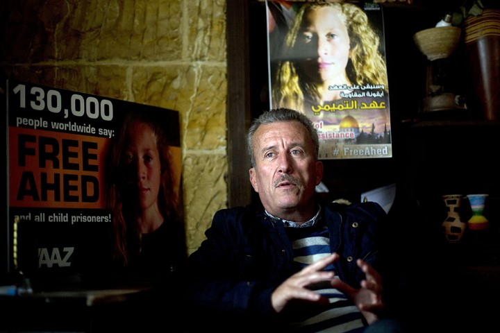 """Palestinian Bassem Tamimi speaks in front of posters showing his daughter Ahed at his home in Nabi Saleh near the West Bank city of Ramallah, on Jan. 5, 2018. Israel's hard-charging prosecution of his 16-year-old daughter who slapped two Israeli soldiers has trained a spotlight on her activist family and its role in what Palestinians call """"popular resistance,"""" or near-weekly protests against Israeli occupation staged in several West Bank villages. (AP Photo/Majdi Mohammed)"""