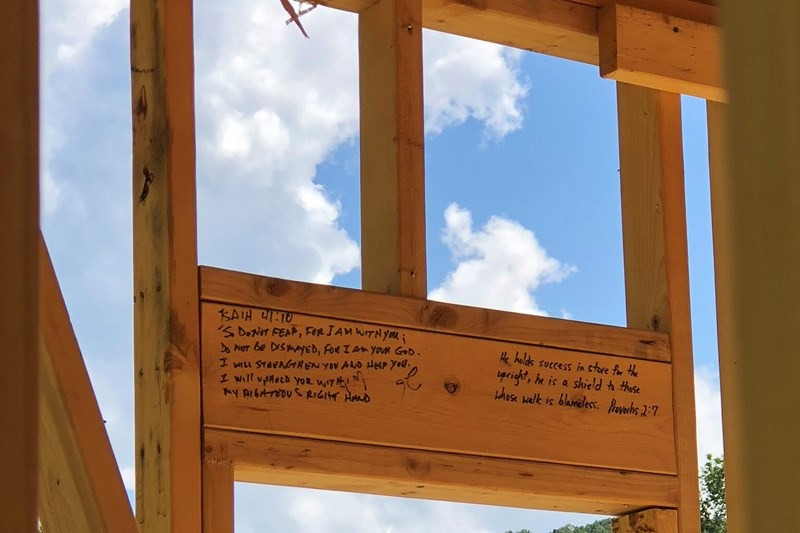 Volunteers pray and write Scriptures on the wood used in each tiny home constructed in The Light Community. Photo provided by Grant Hasty