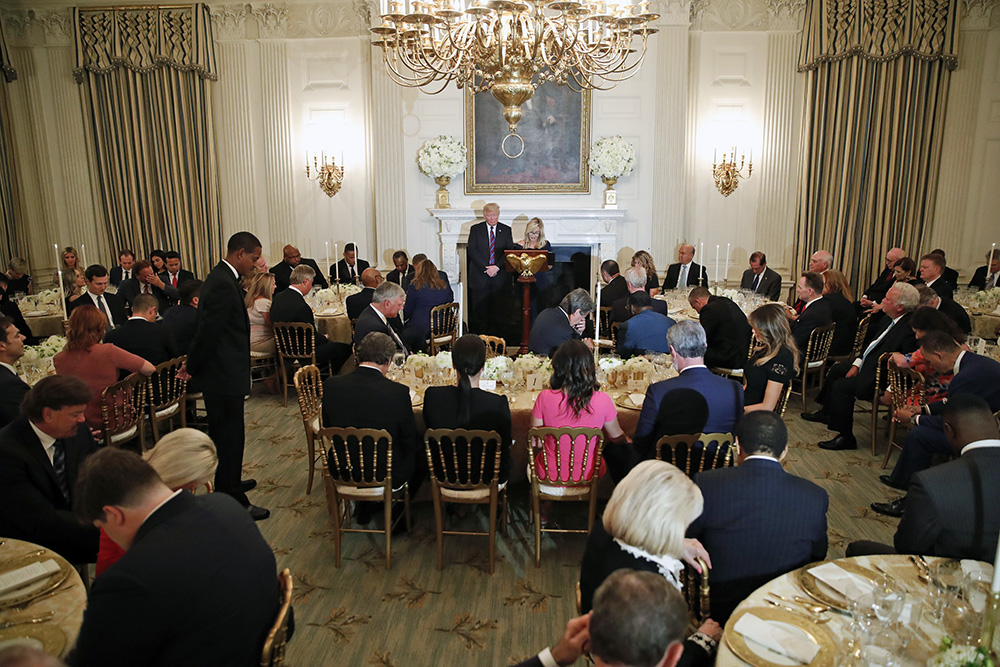 President Donald Trump bows his head in prayer as pastor Paula White leads the room in prayer during a dinner for evangelical leaders in the State Dining Room of the White House onAug. 27, 2018, in Washington. (AP Photo/Alex Brandon)