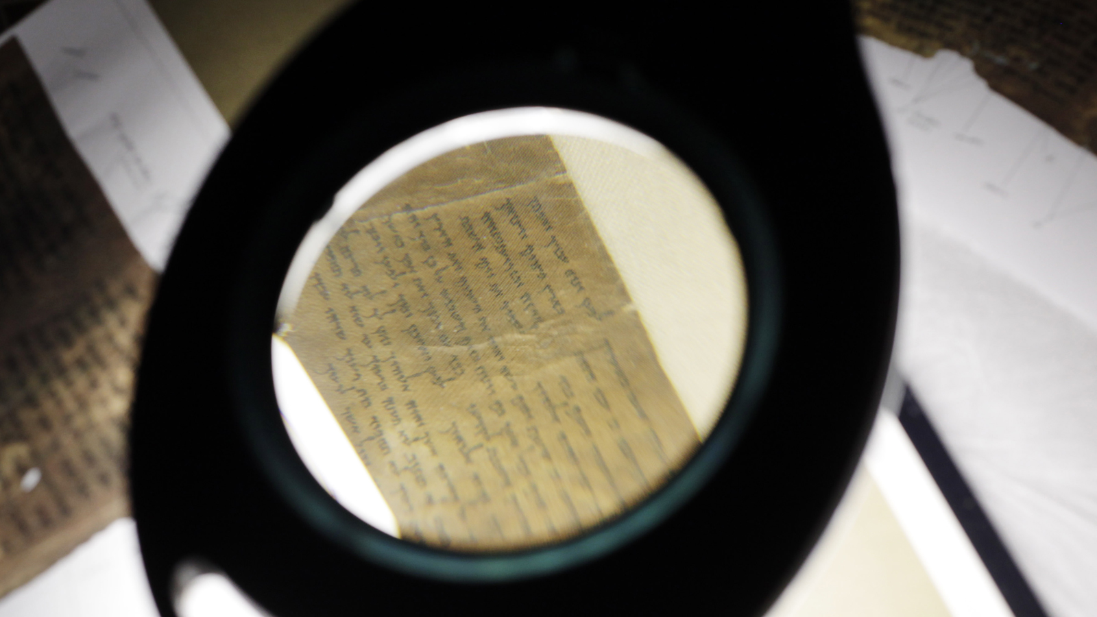 Conservators examine a portion of the Dead Sea Scrolls containing the Ten Commandments before the scrolls' installation at Discovery Times Square in New York, Thursday, Dec. 15, 2011. (AP Photo/Seth Wenig)