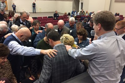 IMB trustees surround and pray for newly-elected IMB President Paul Chitwood and his wife Michelle. Photo by David Roach