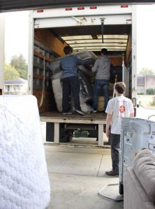 Volunteers loading mattresses