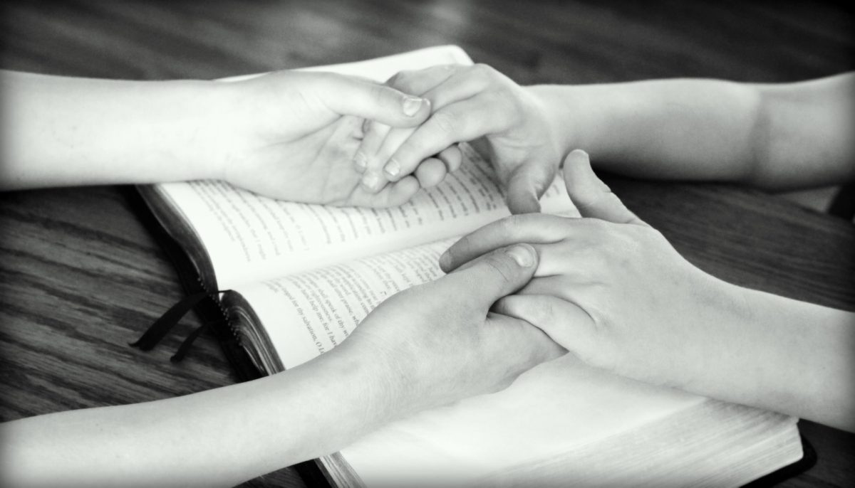 Holding hands over Bible